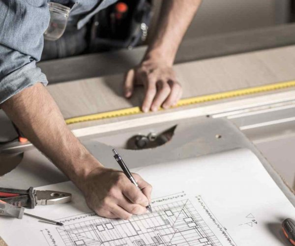 closeup of man working over building plans